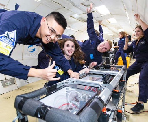 Large group of smiling students performs a research experiment while floating inside the ZERO-G plane. Credit: ZERO-G.