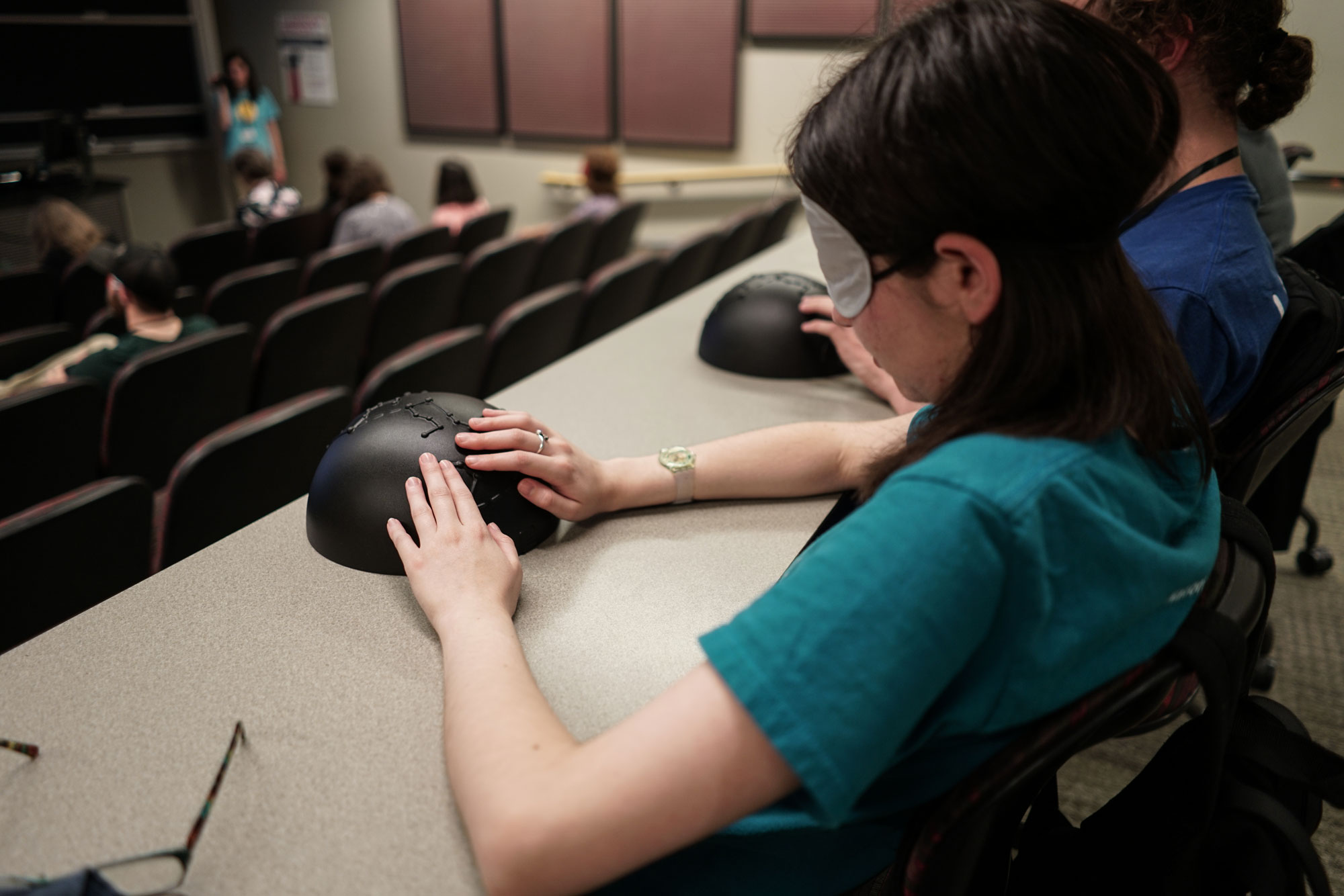 Student wearing a blindfold and feeling a tactile constellation dome during an accessible planetarium show.