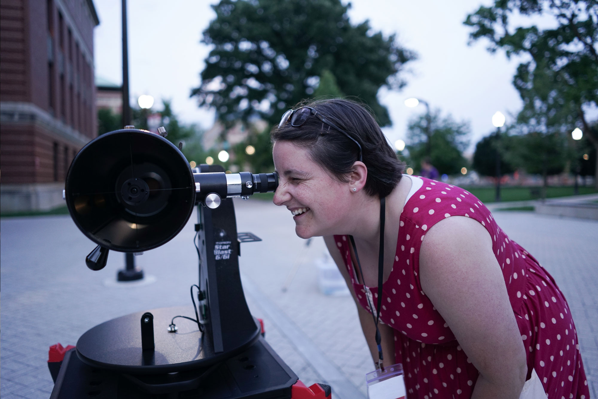 Woman smiling and looking through a telescope at the SciAccess 2019 star party.